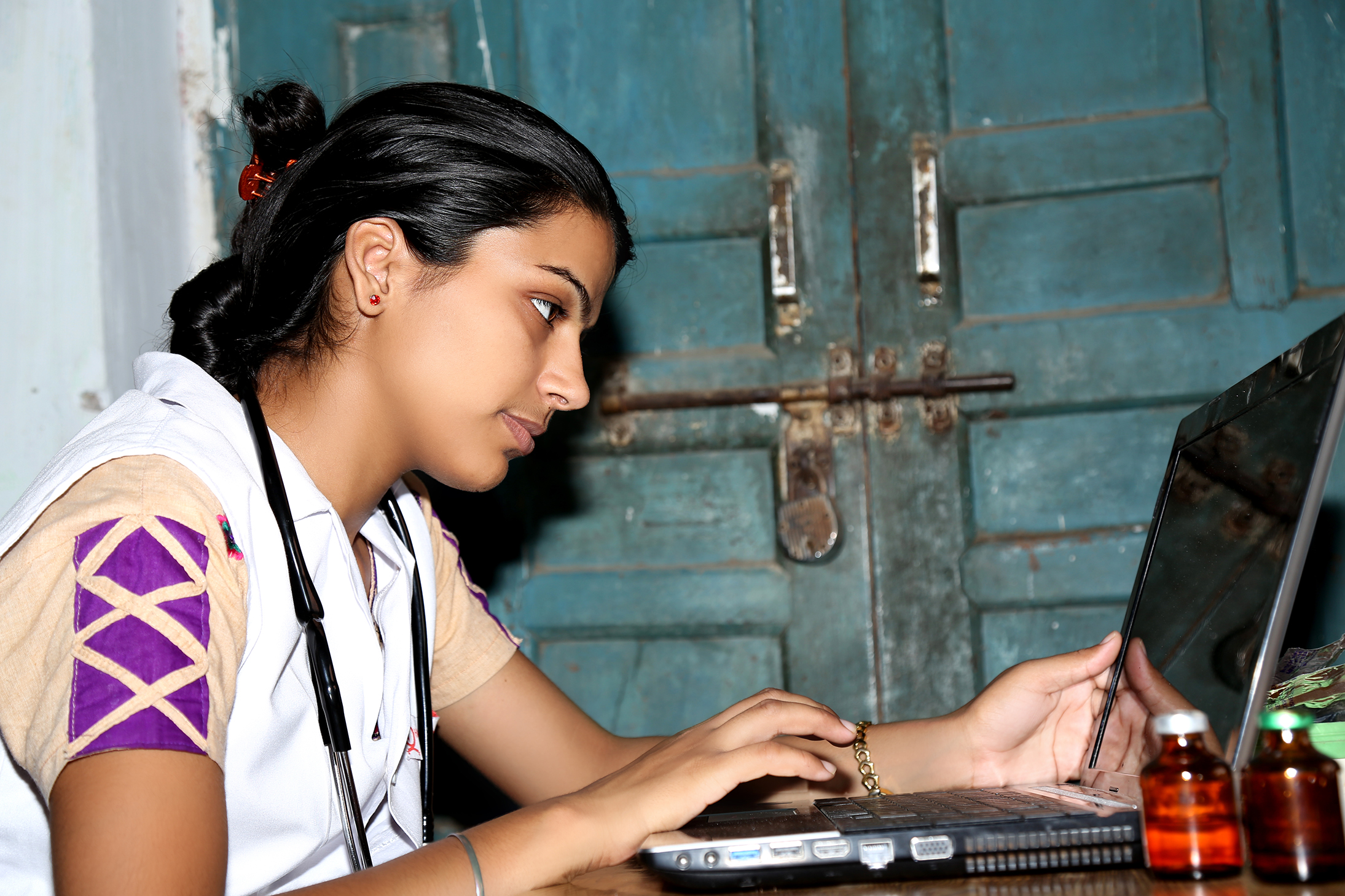 Rural Young Indian Doctor working on Laptop.