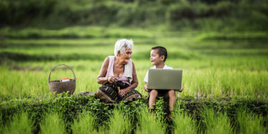 Happy boy and grandmother using laptop, asia thailand.